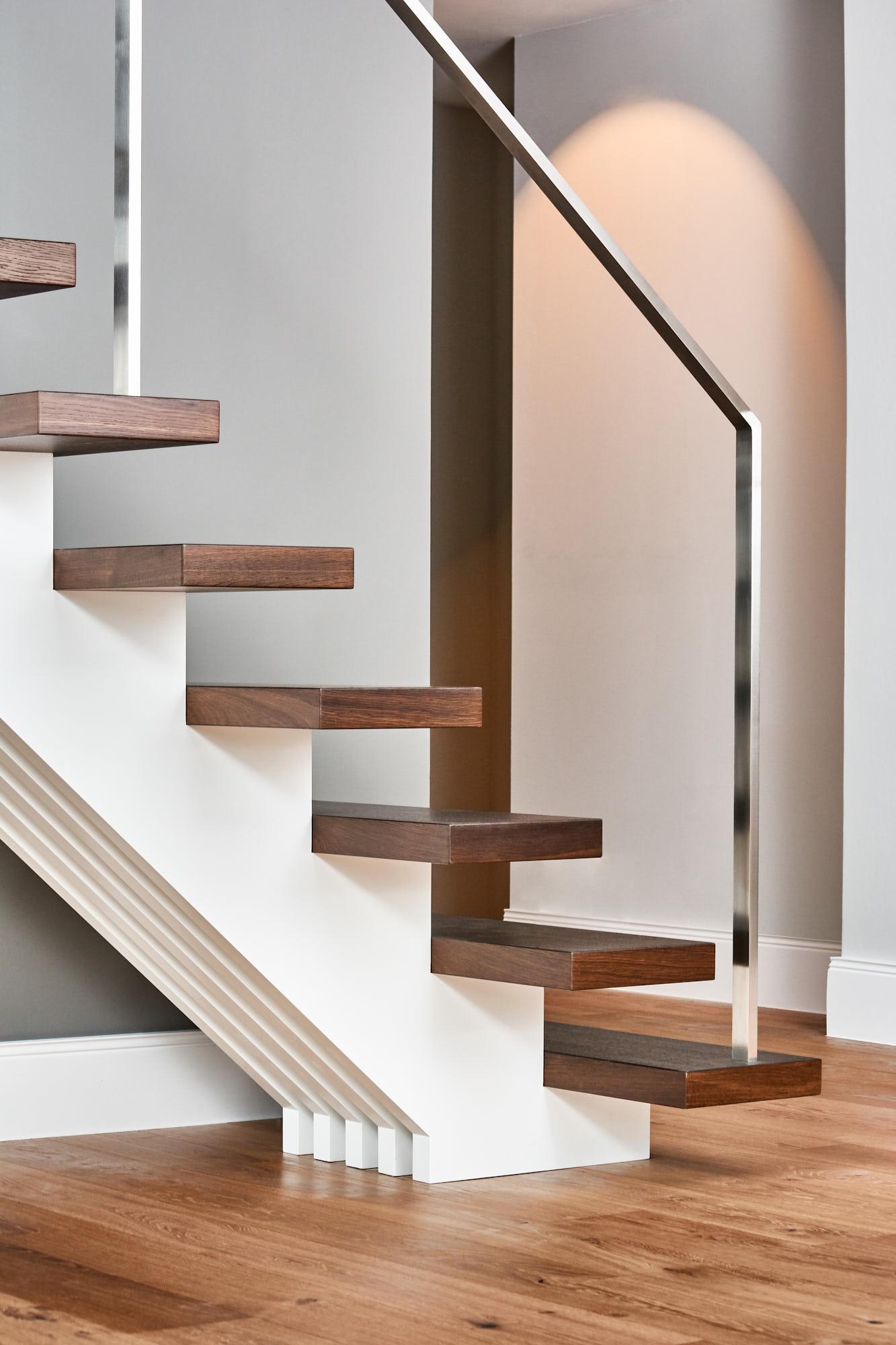 weiße Mittelholmtreppe mit Geländer aus gebürstetem Edelstahl
